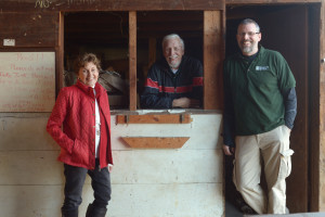 Greg with his mom and dad inside the old auction barn at the window where people signed up for bid numbers.