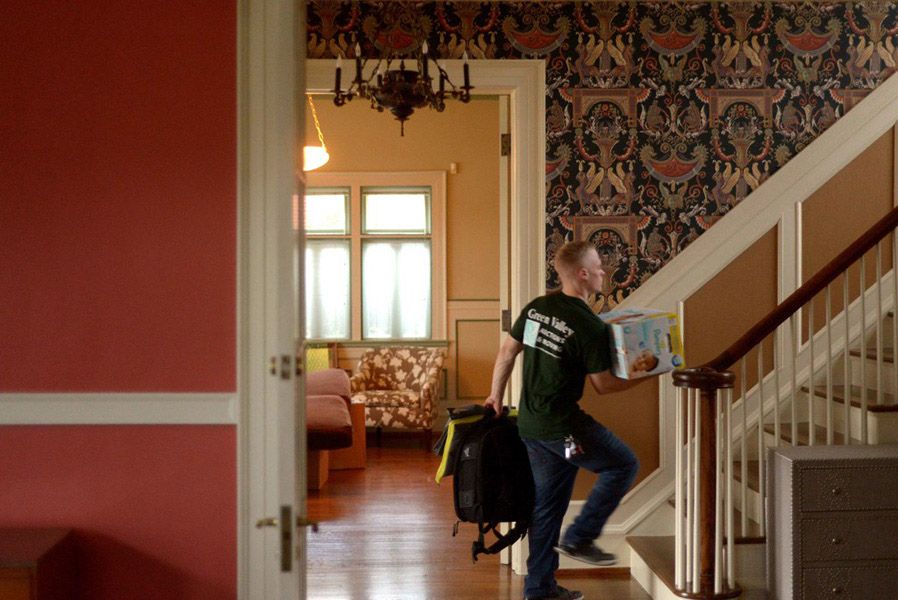 green valley moving company employee carrying a box up the stairs of a home in harrisonburg
