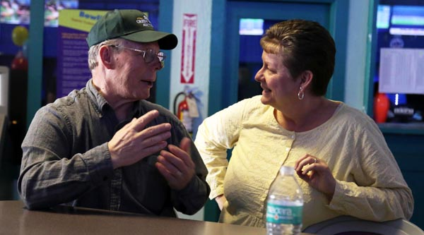 Two Green Valley employees talk as they wait for their turn to bowl