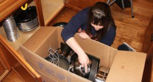 Jessi packing a box as a demonstration on how to pack items in preparation for a move.