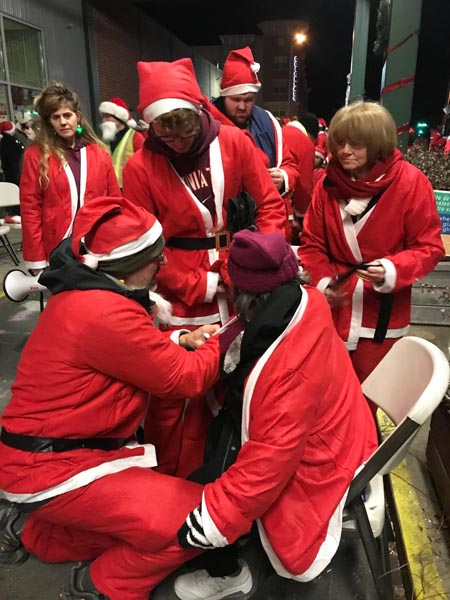 Greg and Scotty Evans helping other Santa runner put on her santa suit