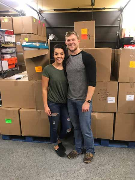 Samuel and Sierra Evans standing in front of pallets of shoe boxes ready to be sorted at New Missions