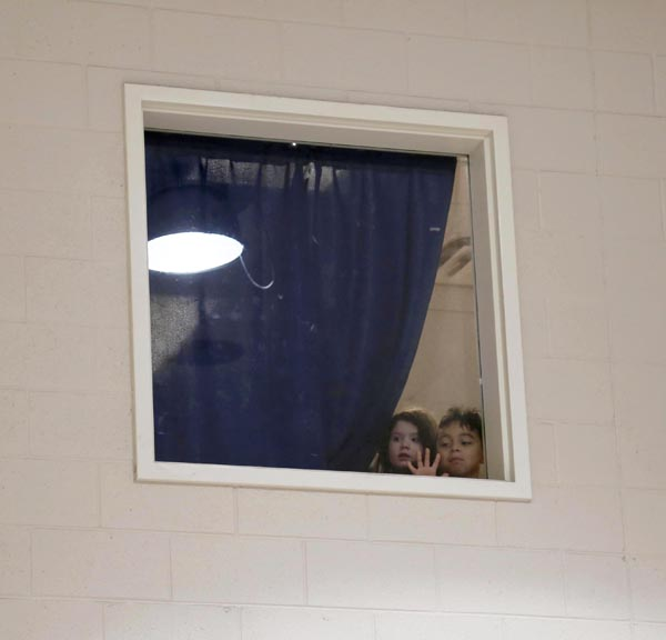 Photo of little boy and girl standing by a window and peering through as they watch the set up of their birthday party