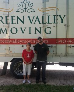 Green Valley Moving employee poses infront of truck with customer who they just moved