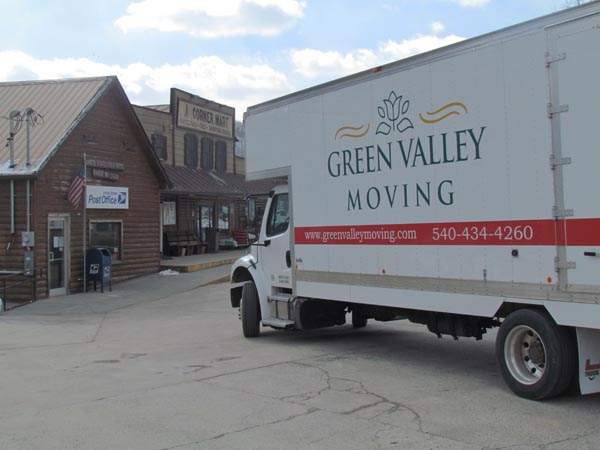 Green Valley Moving truck in front of a store