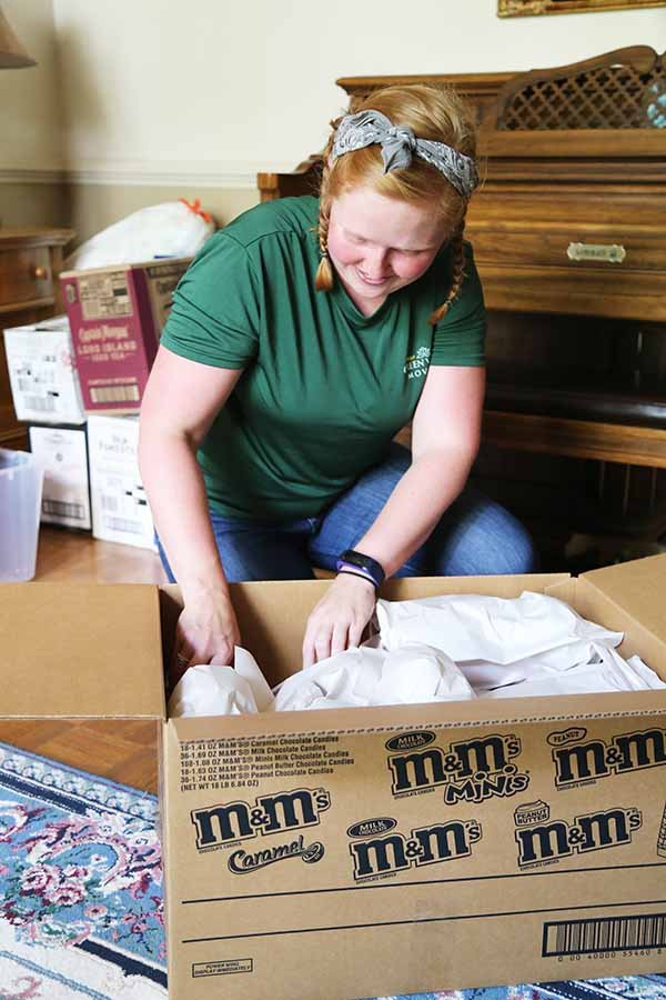 Green Valley Employee packs glassware into a moving box